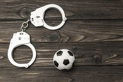 Handcuffs for the detention of sports fans who violate the public. Order. soccer ball stock image