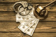 Handcuffs, dollar bills, a judge`s hammer against the background royalty free stock photo