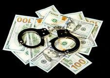 Handcuffs on dollar bills Stock Photography