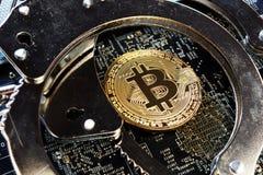 Handcuffs en Bitcoin-muntstuk Misdaad met cryptocurrency stock afbeeldingen