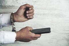Handcuffs en de telefoon van de mensenhand royalty-vrije stock afbeeldingen