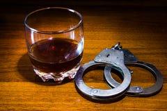 Handcuffs en een Whisky stock afbeeldingen