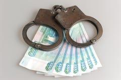 Handcuffs en geld op grijs Royalty-vrije Stock Foto's