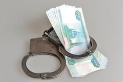 Handcuffs en geld op grijs Royalty-vrije Stock Foto