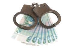 Handcuffs en geld op witte achtergrond Stock Fotografie