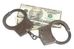 Handcuffs en geld op witte achtergrond wordt geïsoleerd die Stock Afbeelding