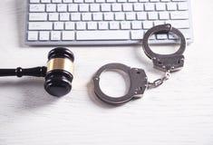 Handcuffs en Rechter Gavel met computertoetsenbord Concept Cyber-misdaad en Online fraude royalty-vrije stock fotografie