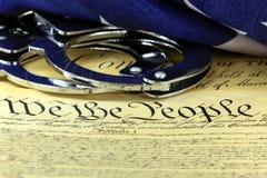 Handcuffs en vlag op de Grondwet van de V.S. - Vierde Amendement stock fotografie