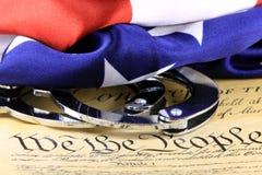 Handcuffs en vlag op de Grondwet van de V.S. - Vierde Amendement stock foto's