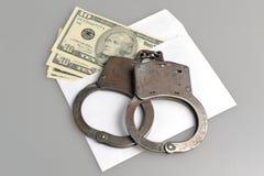 Handcuffs en witte envelop met geld op grijs Stock Foto's