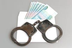 Handcuffs en witte envelop met geld op grijs Stock Foto