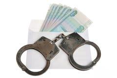 Handcuffs en witte envelop met geld op witte achtergrond Royalty-vrije Stock Afbeelding