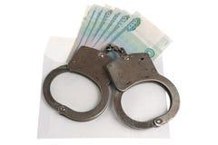 Handcuffs en witte envelop met geld op witte achtergrond Royalty-vrije Stock Foto