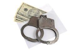 Handcuffs en witte envelop met geld op witte achtergrond Stock Foto