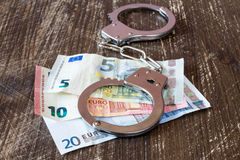 Handcuffs and euro currency. Royalty Free Stock Images