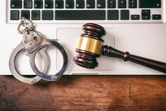 Handcuffs and a gavel on a computer on a wooden background, copy space. Cybercrime and law concept. Handcuffs and a judge gavel on a computer on a wooden Royalty Free Stock Photos