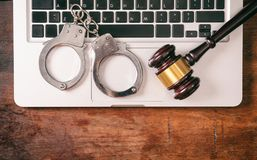 Handcuffs and a gavel on a computer on a wooden background, copy space. Cybercrime and law concept. Handcuffs and a judge gavel on a computer on a wooden Stock Images