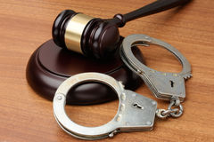 Handcuffs and gavel on a wood surface Royalty Free Stock Photo