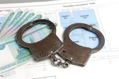 Handcuffs, geld met het plan van het geïsoleerde huis Stock Foto
