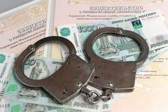 Handcuffs, geld op de achtergrond van de eigendomscertificaten Stock Foto's