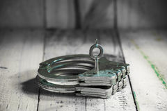 Handcuffs on grunge wooden Stock Images