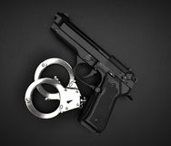 Handcuffs and gun on the black table. Handcuffs and hand gun on the black table Stock Photography