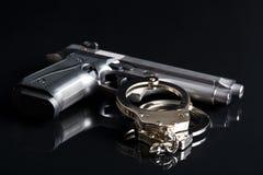 Handcuffs and handgun Royalty Free Stock Photography