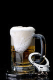 Handcuffs on the handle of a beer mug Royalty Free Stock Images