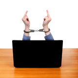 Handcuffs on Hands behind Laptop Royalty Free Stock Photography