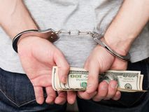 Handcuffs on hands holding money Stock Image