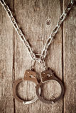 Handcuffs hanging on the chain Stock Photos