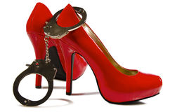 Handcuffs and high heels. Close up, on white background Stock Image
