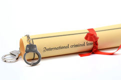 Handcuffs and International criminal law document. Handcuffs and International criminal law, law concept Stock Photos