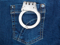 Handcuffs in jeans pocket Royalty Free Stock Images