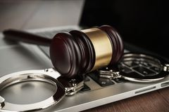 Handcuffs and judge gavel on computer Royalty Free Stock Photo