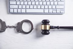 Handcuffs and Judge Gavel with computer keyboard. Concept of Cyber crime and Online fraud stock photos