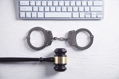 Handcuffs and Judge Gavel with computer keyboard. Concept of Cyber crime and Online fraud stock photo