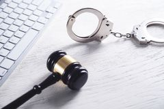 Handcuffs and Judge Gavel with computer keyboard. Concept of Cyber crime and Online fraud royalty free stock photo