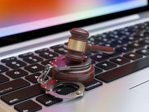 Handcuffs and judge gavel on the laptop keyboard Stock Image