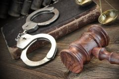 Handcuffs, Judge Gavel And Old Law Books On Wooden Table Royalty Free Stock Image