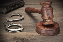 Handcuffs, Judge Gavel And Old Law Books On Wooden Table Royalty Free Stock Images