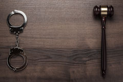 Handcuffs and judge gavel on wooden background Royalty Free Stock Photo