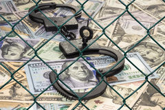 Handcuffs with the key on the background of dollars under wire netting (lattice) Stock Photos