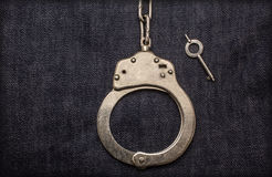 Handcuffs with a key on jeans. Background Stock Image
