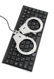 Handcuffs on keyboard isolated Royalty Free Stock Image
