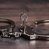 Handcuffs and keys on brown wooden table Royalty Free Stock Photos