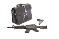 Handcuffs a leather case a gun and a m4-rifle Royalty Free Stock Photo