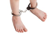 Handcuffs or legcuffs on legs Stock Photography