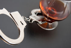 Handcuffs lock with glass on background Royalty Free Stock Photography