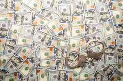 Handcuffs lying on background of dollars banknotes. top view royalty free stock photography